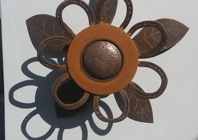 Wall.Flower: car brake disks, marine pipe, horseshoes, steel plate offcuts.